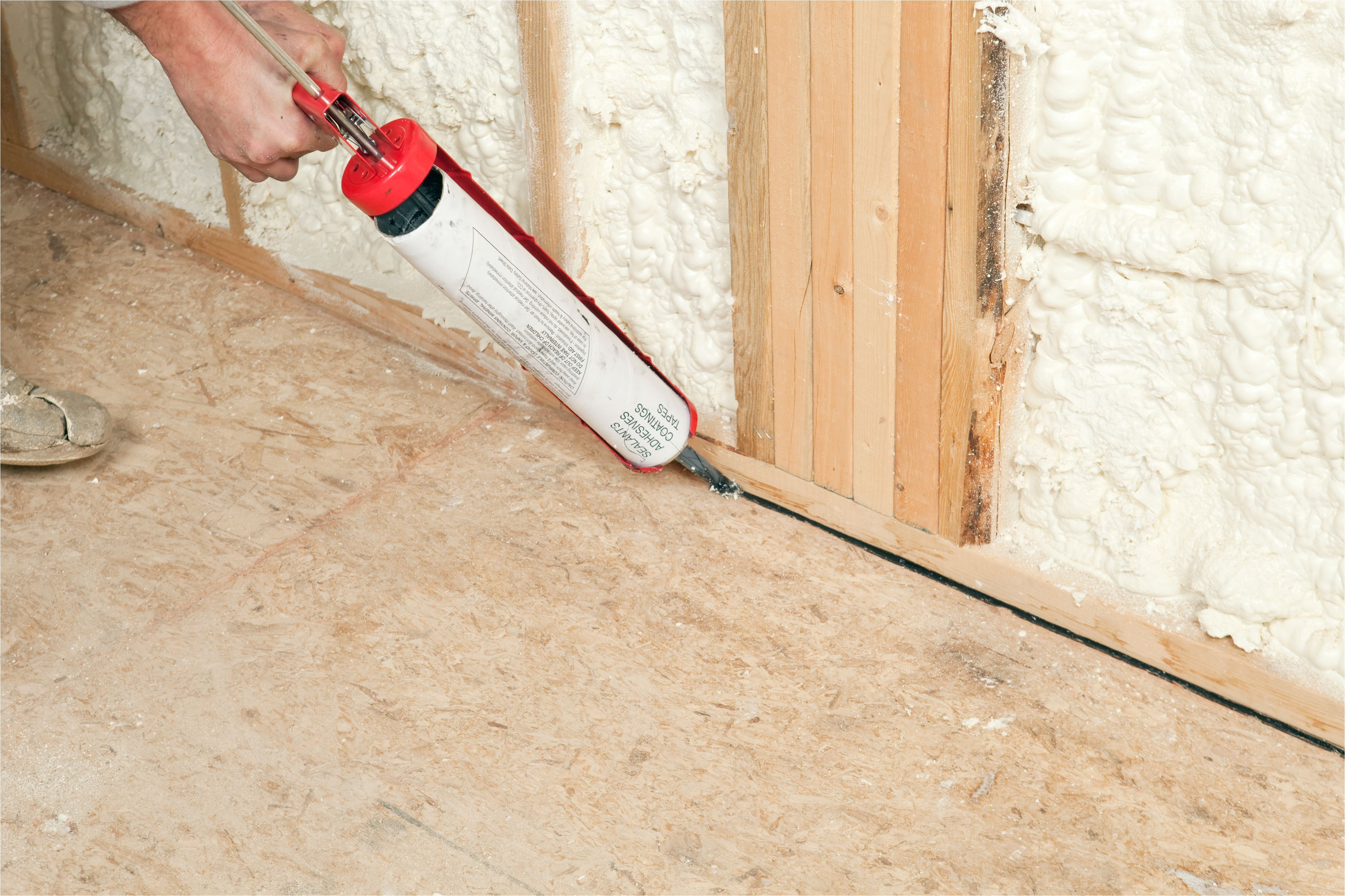 worker caulking wall plate to subfloor 185099682 57fa64803df78c690f7666e2 jpg