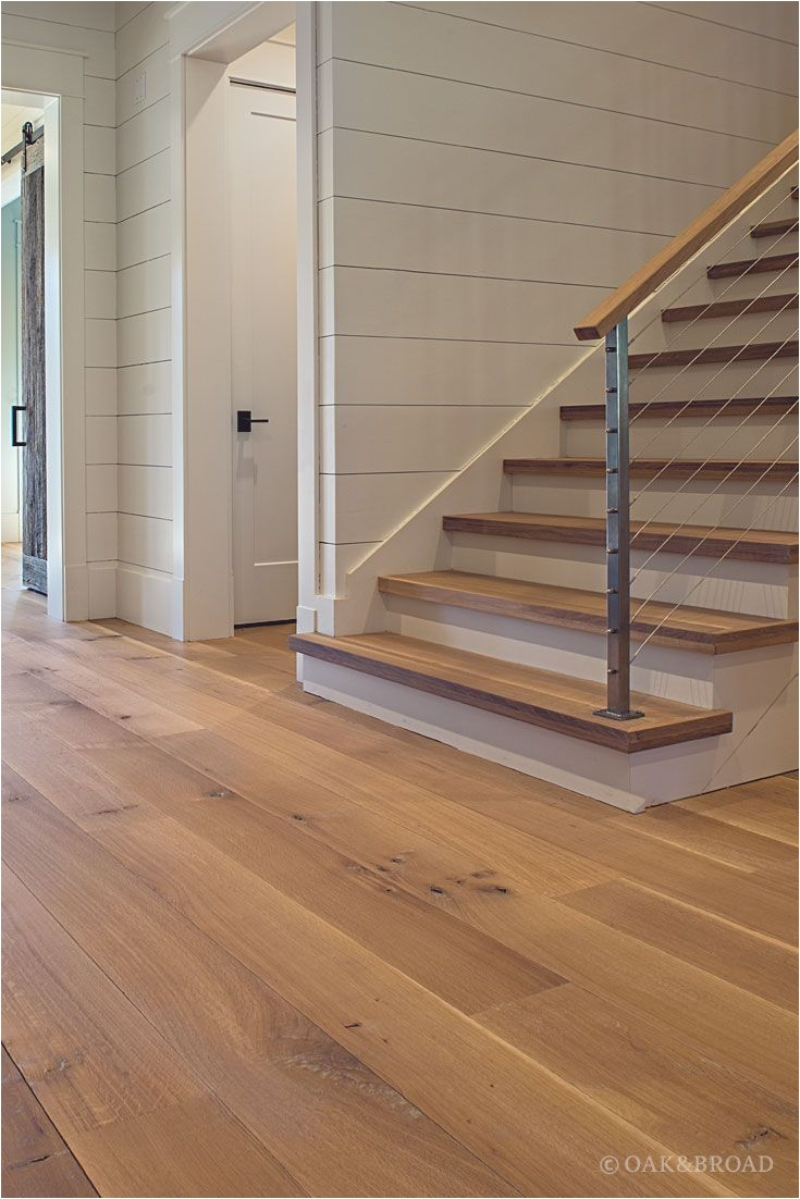 wide plank white oak hardwood floor by oak and broad with custom stain matching stair treads discover more at