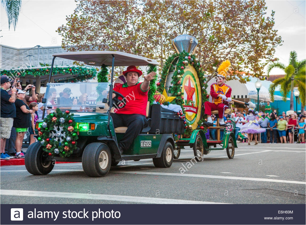 man driving decorated golf cart pulling large bass drum in macy s holiday parade at universal studios
