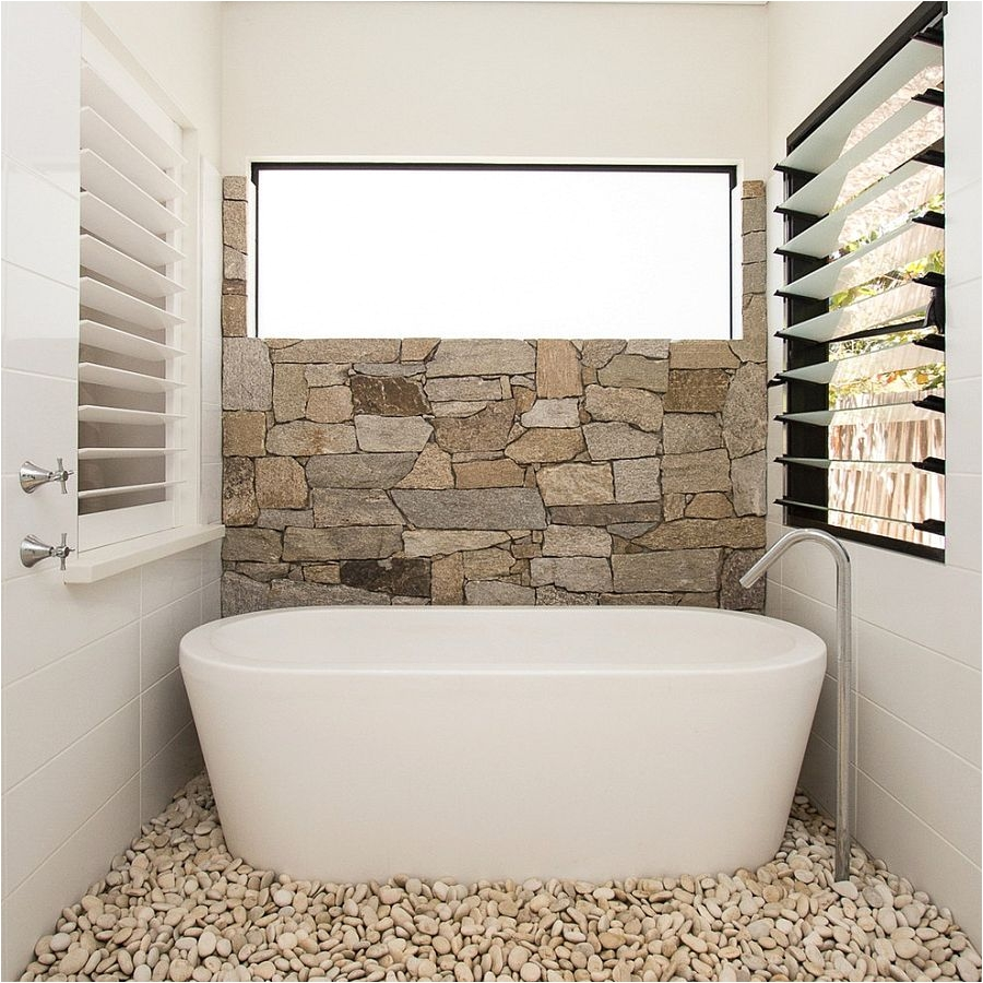 Half wall in natural stone and pebbles on the floor turn the the small bathroom into a relaxing hub [Design Sam Davison Interiors]