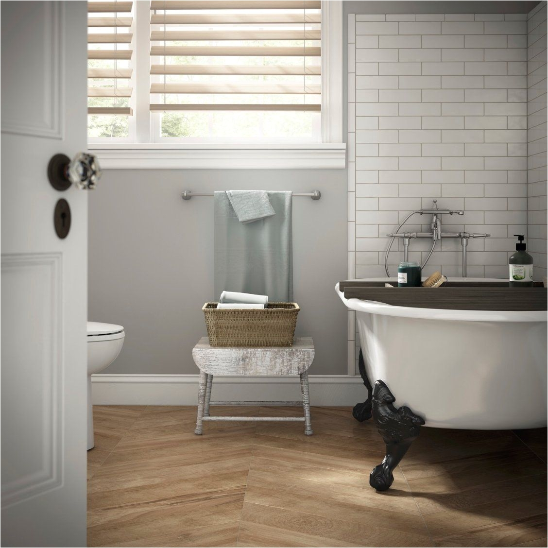 Create a spa like bathroom with soft gray walls a clawfoot tub striking herringbone floors and classic white subway tiles around the tub