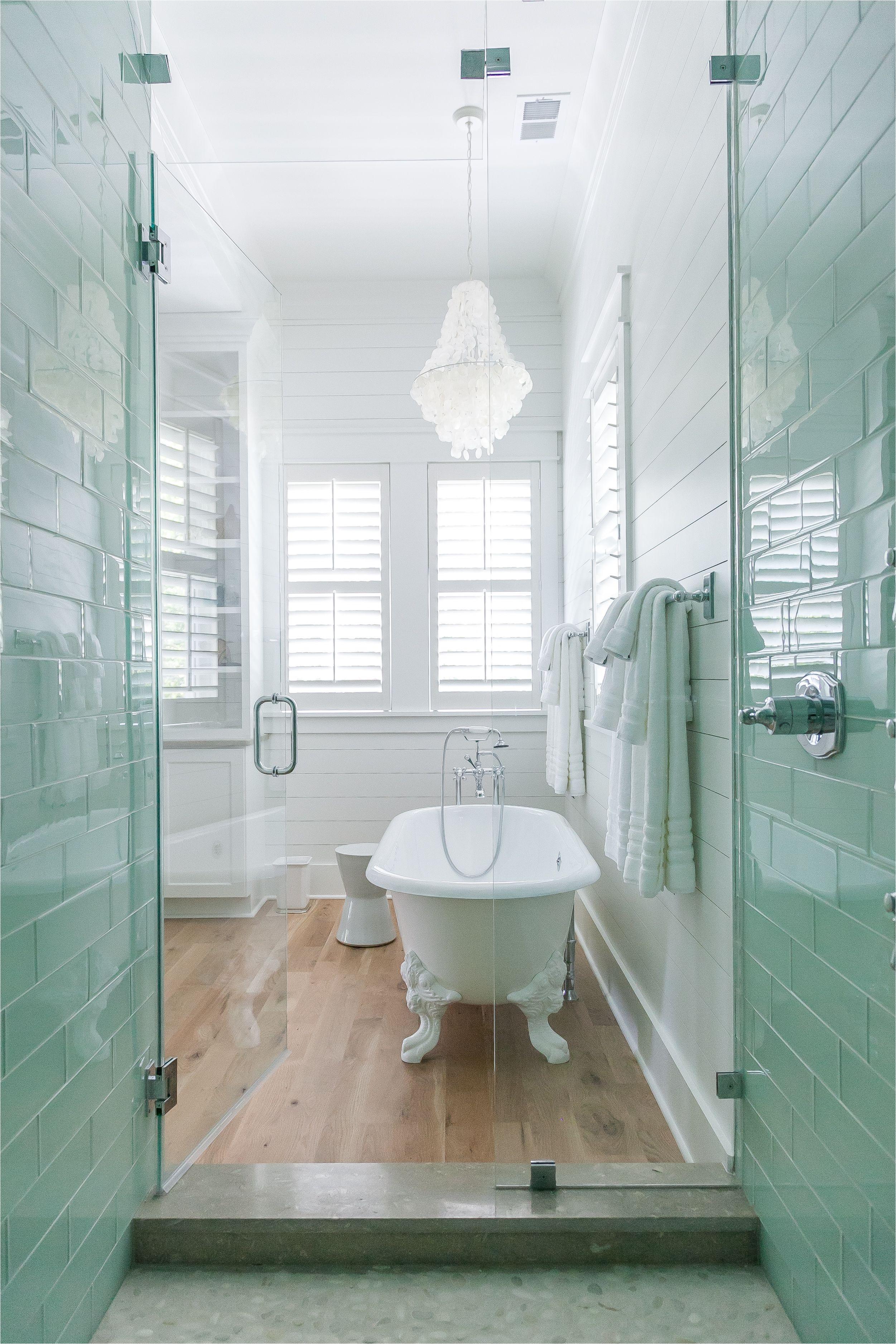 Coastal Master Bathroom with white oak floors claw foot tub white oak floors sea glass cabinet pulls and seafoam glass shower subway tile